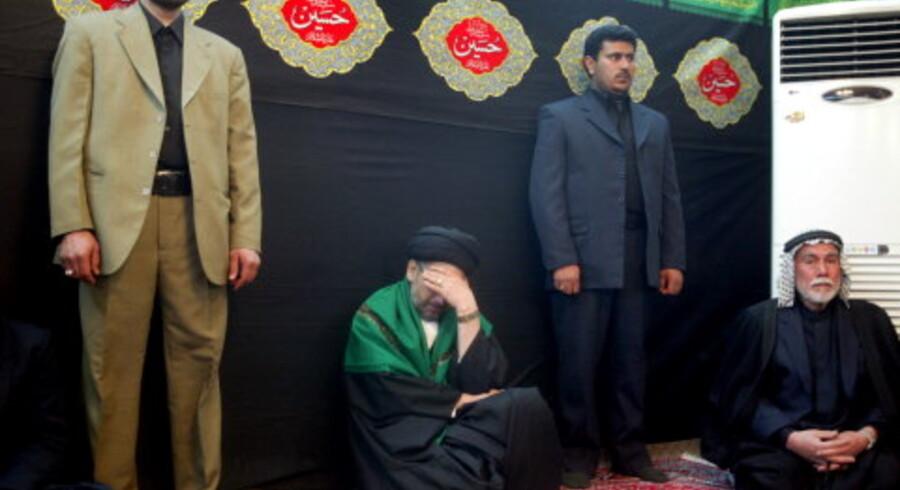 Den shiamuslimske Forenede Irakiske Alliances leder<br>Abdel Aziz al-Hakim (med<br>grøn kappe over skulderen) brød grædende sammen, da<br>det i går stod klart, at shiamuslimerne ikke havde fået over halvdelen af stemmerne. Foto: Akram Saleh/Reuters