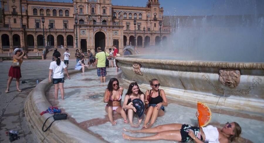 Den europæiske sommer 2018 har været ekstremt varm. I Sevilla køler turister og lokaler af i et springvand på Plaza de Espana. AFP PHOTO / JORGE GUERRERO