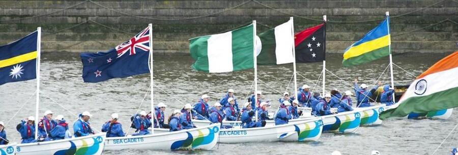 Motorbåde med Commonwealth-landenes flag sejler ned af Themsen.
