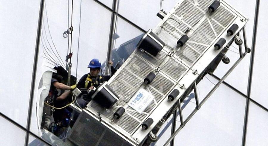 Her hjælper brandfolk de to vinduespudsere i sikkerhed ved at skære hul i en rude på 69. sal.