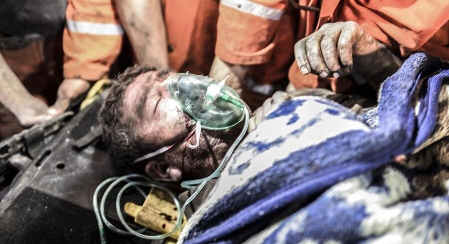 En tilskadekommen minearbejder bæres ud efter eksplosiosnulykken.