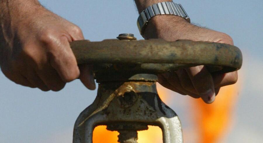 En irakisk oliearbejder drejer på hanen ved Shirawa-feltet tæt på byen Kirkuk. Irak er en del af OPEC, der netop har øget produktionen.