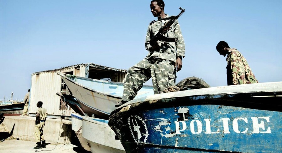 Det lokale politi i Bosaso, Somalia, viser politibåden frem. I baggrunden konfiskerede piratbåde.