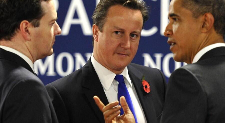Fra venstre diskuterer finansminister George Osbourne, premierminister David Cameron og USAs præsident Barack Obama verdens tilstand på G20-topmødet for nylig. Krisen får nu Storbritannien til at indføre en højere skat på bankers transaktioner.
