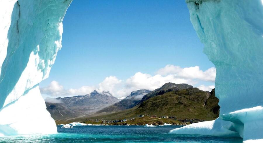 """Et femstjernet """"turist-isbjerg"""" i fjorden ud for den sydgrønlandske by, Narsaq. I hullet ses den vestlige del af byen Narsaq, samt det høje Ilimmaasaq fjeldmassiv og yderst til venstre, det uranholdige Kvanefjeld. Juli 2010."""