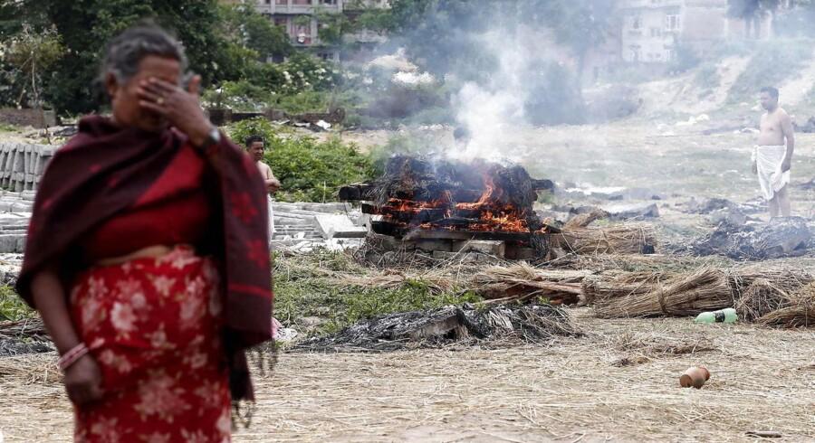 En lokal kvinde græder foran et bål, hvor nogle af ofrene for jordskælvet bliver brændt efter lokale begravelsesskikke.