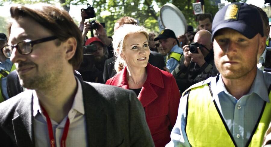 Helle Thorning-Schmidt forlader under massiv politibeskyttelse Fælledparken efter sin tale, mens en protestgruppe råber skældsord og fløjter af hende.