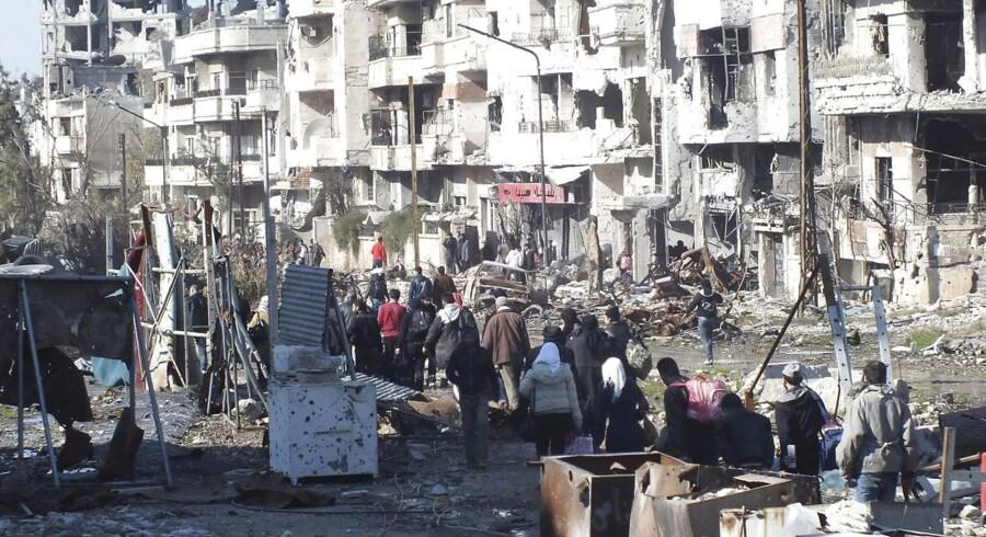 Flygtninge på vej til et opsamlingssted under evakueringen i Homs tidligere på ugen.