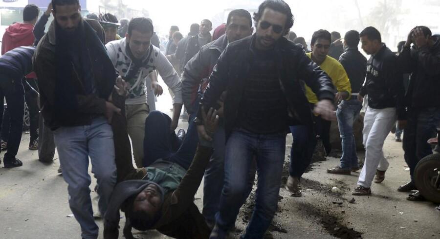 Støtter af Det Muslimske Broderskab og den afsatte præsident Mohamed Morsi bærer en såret demonstrant væk i Kairo.