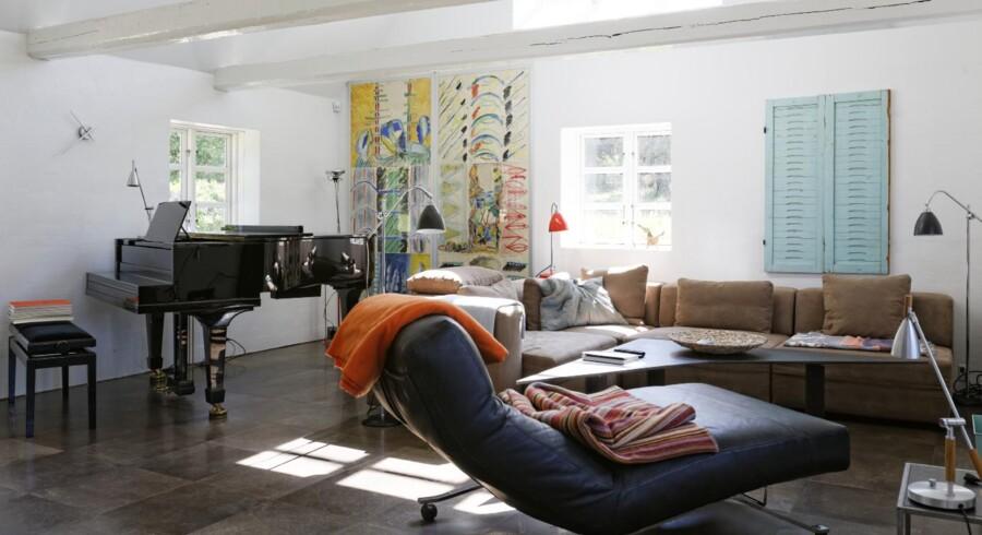 Stuen er åben til kip med stort vindue mod øst. Sofabordet er udført af en smed efter Vibeke Dahms udkast, og chaiselongen er fra Eilersen. Kunstværket med vandfarve på papir er af en ukendt, finsk kunstner og fra cirka 1980. De antikke, vandgrønne skodder er franske.