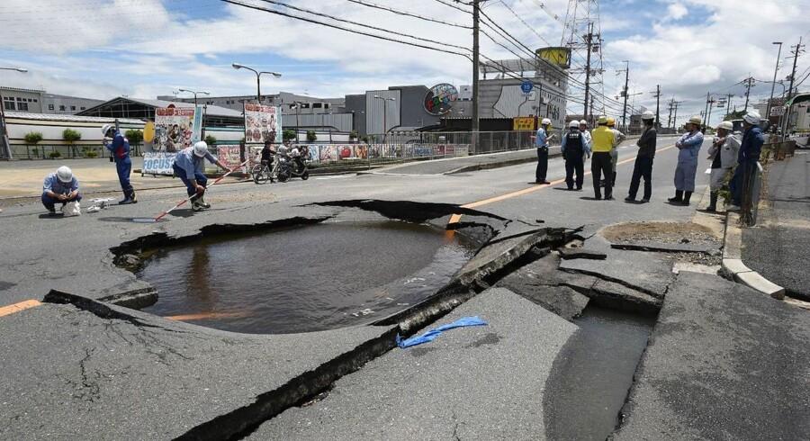 Der arbejdes ved en delvist ødelagt vej efter jordskælvet lidt nord for storbyen Osaka 18. juni 2018. Flere er dræbt og mindst 200 såret.