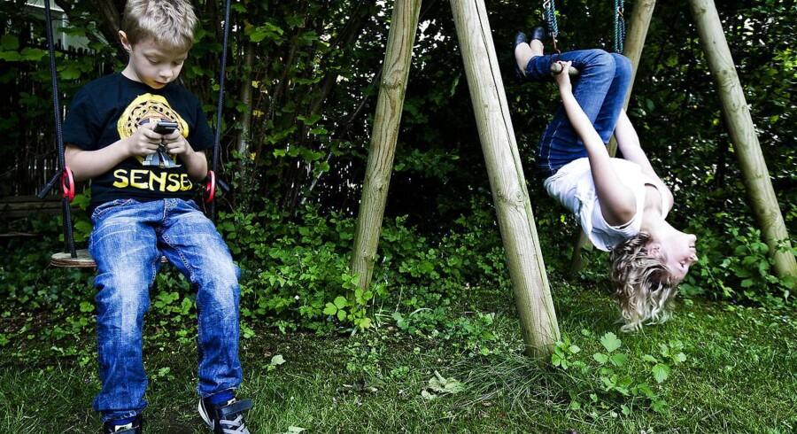 Arkivfoto: August på 8 år med sin mobil, mens søster Astrid på 10 år leger.