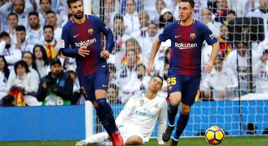 Cristiano Ronaldo ærgrer sig efter at have tabt bolden til Barcelonas Thomas Vermaelen (t.h.) og Gerard Pique.