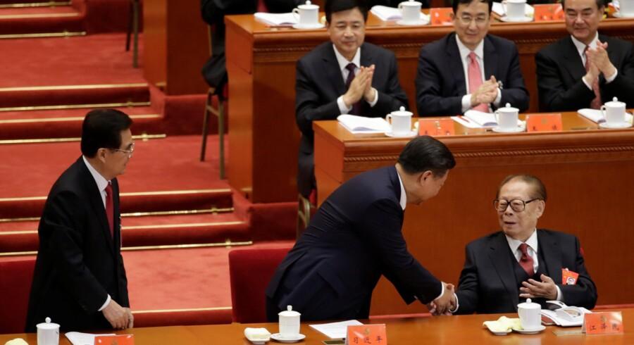 Xi Jinping (i midten) giver hånd til tidligere præsident Jiang Zemin. Når kongressen er slut, vil det stå klart, i hvor høj grad det er lykkedes den magtfulde præsident at forme partiets top.