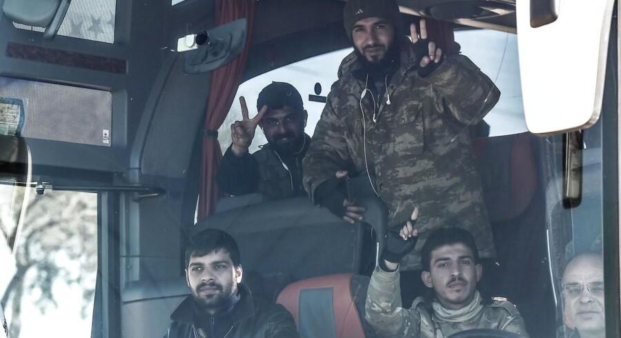 Tyrkisk-støttede syriske rebeller hilder under transport i det nordlige Syrien. Her kæmper de side om side med den tyrkiske hær i et forsøg på at fortrænge den syrisk-kurdiske milits, YPG, der har kontrolleret området siden 2012 og er allieret med USA og Europa. / AFP PHOTO / OZAN KOSE