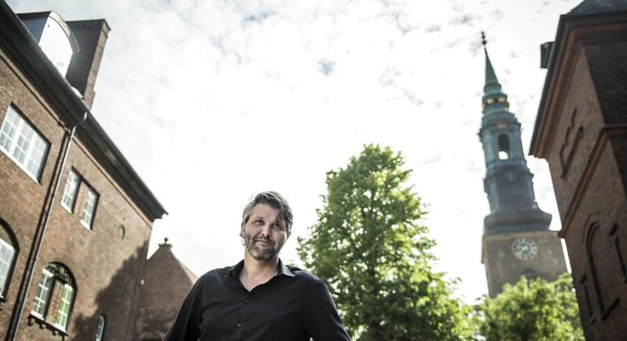 Formand for Sankt Petri Skoles bestyrelse, Marc-Christoph Wagner, fotograferet fra skolegården med Sankt Petri Kirkes spir i baggrunden.