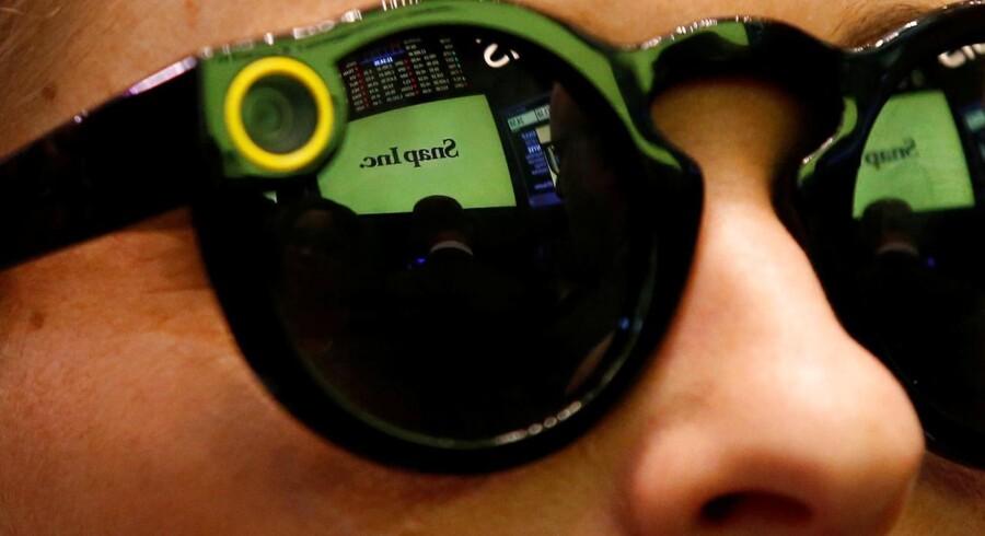 Snapchat, som især mange unge bruger, er nu en børsnoteret virksomhed. Snap, som selskabet bag den populære billedtjeneste hedder, er for nylig begyndt at producere solbriller med indbygget kamera, der kan sende »snaps« direkte. Her holder en snapchatentusiast øje med kursen på New Yorks børs. Foto: Brendan McDermid, Reuters/Scanpix