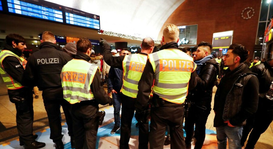 Tysk politi tjekker unge mænds identitet på banegården i Köln nytårsnat.