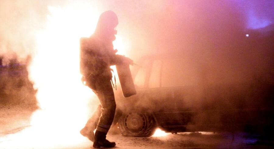 Arkivfoto: Brandmand forsøger at slukke bilbrand i Malmø, 15. august 2016. (Johan Nilsson / Ritzau Scanpix)