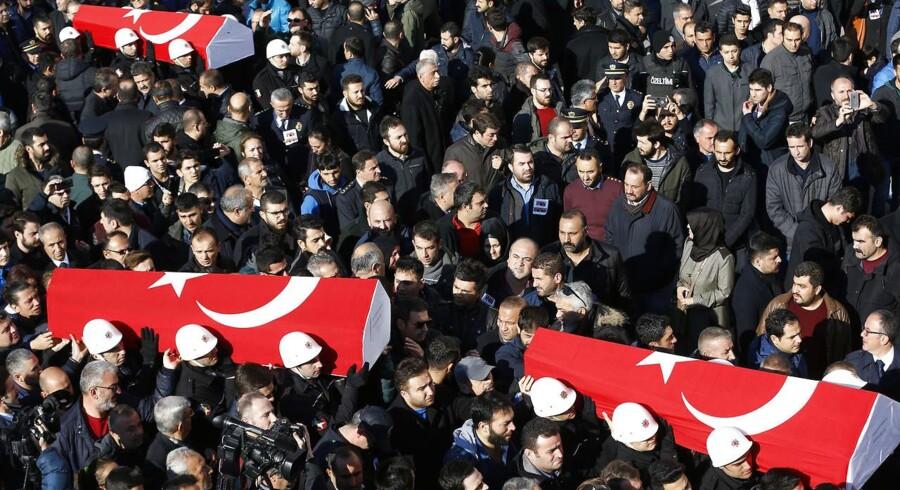 De dræbte politibetjente blev båret i kister svøbt i det tyrkiske flag gennem Istanbul i går. Foto: Murad Sezer