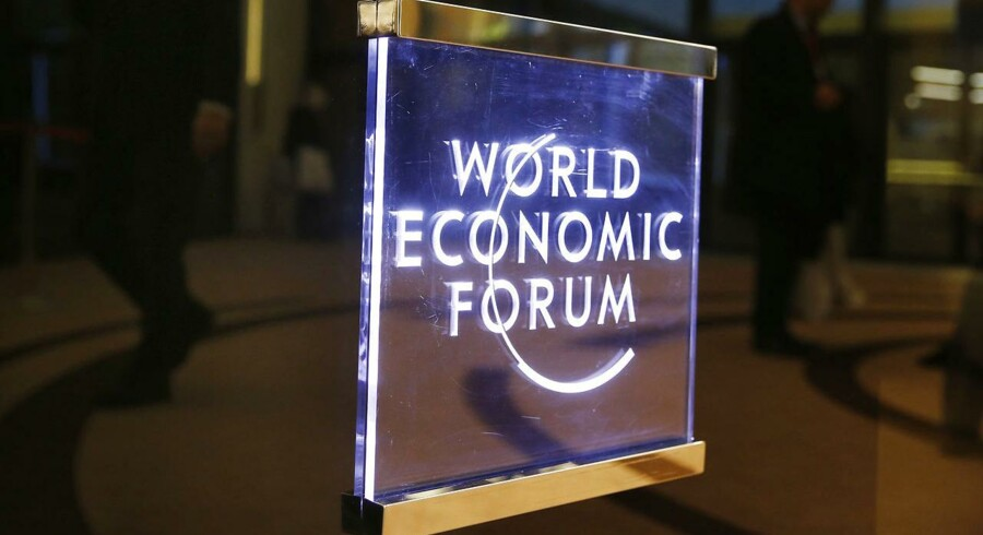 Attendees walk past a sign in the Congress Hall during the annual meeting of the World Economic Forum (WEF) in Davos, Switzerland, January 17, 2017. REUTERS/Ruben Sprich