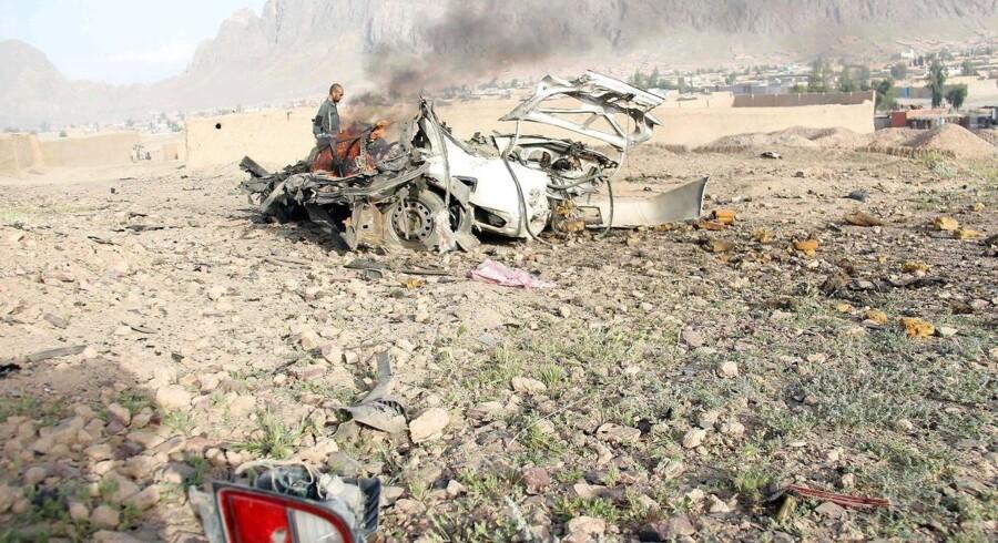 En afghansk politimand inspicerer en selvmordsbombers bil efter et angreb i april. Det krigsplagede land er hårdt ramt af selvmords- og terrorangreb. 30. maj døde op mod 150 personer i Kabul ved det værste terrorangreb i årevis.