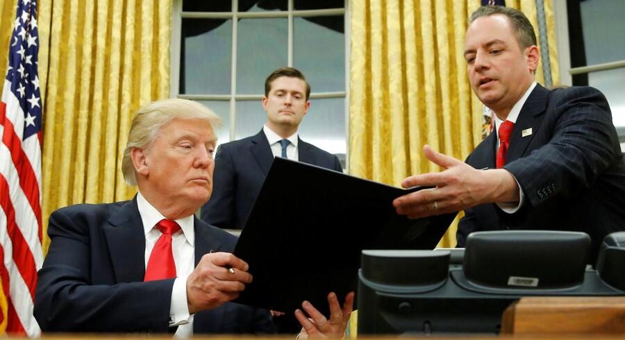Trump overrækker ordren til Reince Priebus.