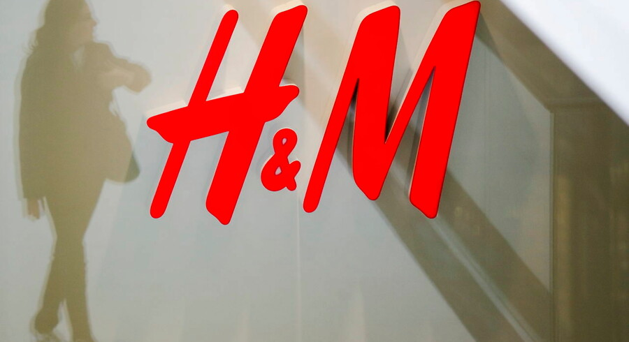 A woman is reflected next to the logo of the H&M fashion retailer in the newly opened Mall of Berlin shopping centre in Berlin, Germany, in this September 25, 2014 file photo. Swedish fashion retailer Hennes & Mauritz reported on February 15, 2016 a 7 percent year-on-year rise in January sales in local currencies, in line with a preliminary figure. REUTERS/Thomas Peter/Files