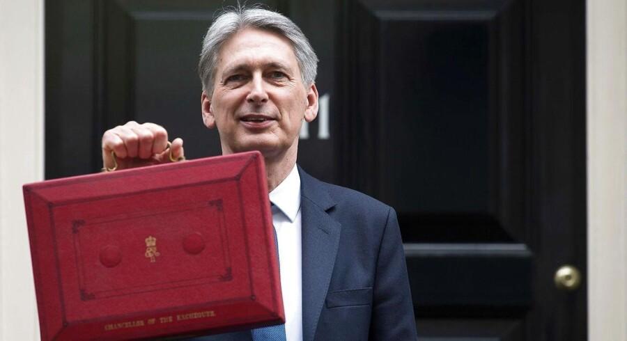 Den britiske finansminister, Philip Hammond, puttede traditionen tro sit finanslovsforslag i den lille, røde kuffert inden præsentationen i Underhuset. Men tallene i den britiske økonomi kan hurtigt ændre sig, hvis EU-udmeldelsen som lovet af regeringen bliver udløst i marts. Foto: AFP