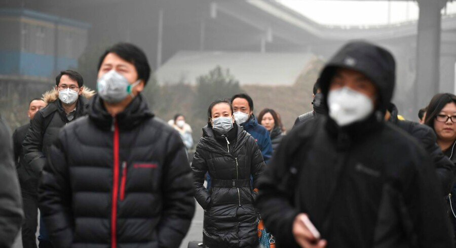 Commuters wear masks on a polluted day in Beijing on December 20, 2016. Heavy smog suffocated northeast China for a fifth day on December 20, with hundreds of flights cancelled and road and rail transport grinding to a halt under the low visibility conditions. / AFP PHOTO / Greg Baker