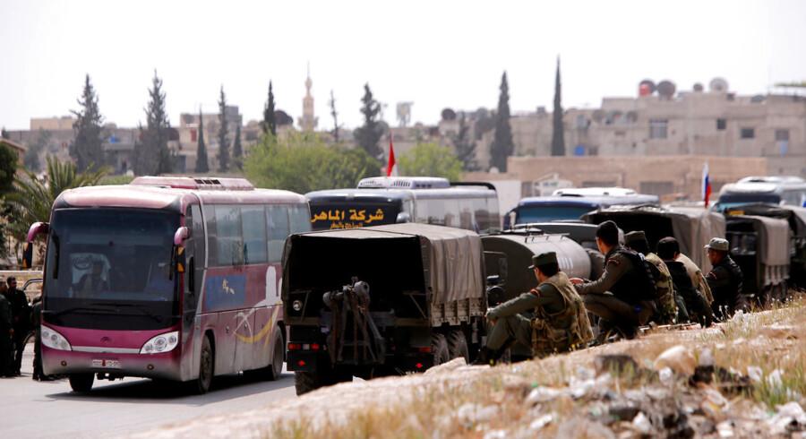 Busser med oprørere og deres familier forlader Douma, mens regeringshæren ser til. Foto: Omar Sanadiki/Reuters