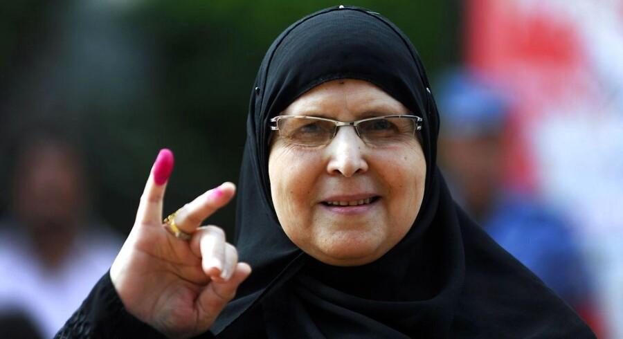 En kvinde fremviser blækket på sien fingre efter at have afgivet sin stemme i Alexandria i det nordlige Egypten, hvor der søndag blev taget hul på et valg, som imidlertid ikke ser ud til at blive nogen gyser. Tværtimod ser præsident al-Sisi allerede ud til at have sat kursen mod en periode med et mageligt parlament, der hverken kan eller vil spænde ben for hans ambitioner.
