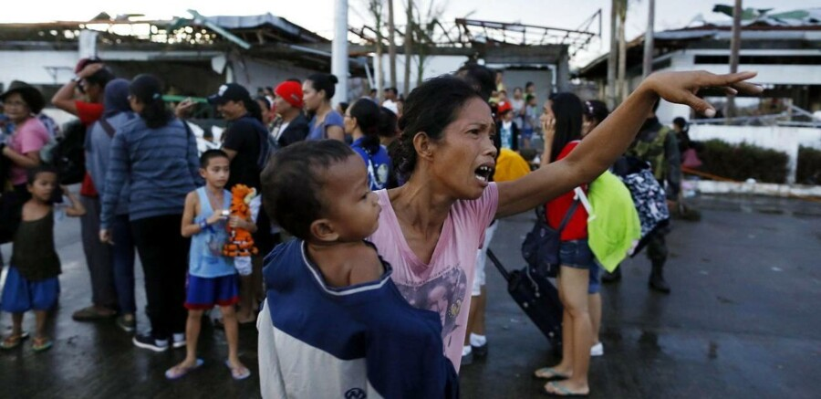 Tyfonramte familier gør klar til at blive evakueret fra lufthavnen i Tacloban til hovedstaden Manila. FN appellerer om 300 millioner dollar til nødhjælp til Filippinerne.