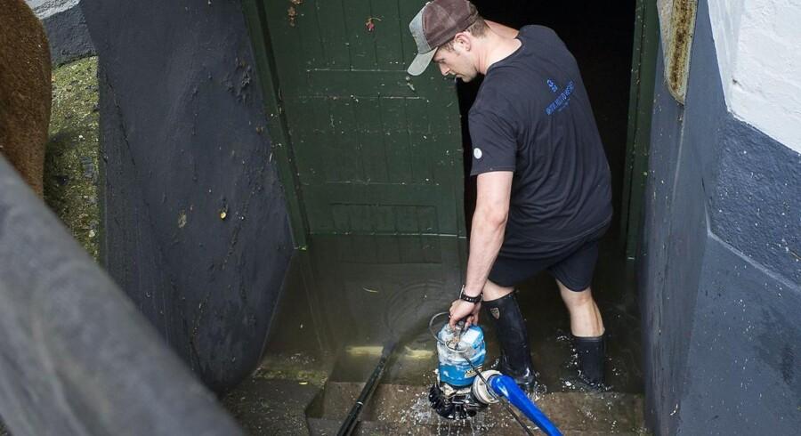 Vand pumpes op fra en kælder i Store Kongensgade, som blev hårdt ramt af lørdagens kraftige skybrud.