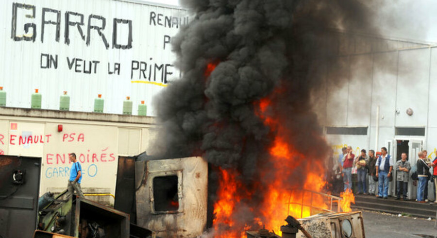 Arbejdere truer  med at sprænge en bildelsfabrik i Châtellerault i det vestlige Frankrig i luften. Skiltene kræver, at Renault betaler erstatning for fyringer.