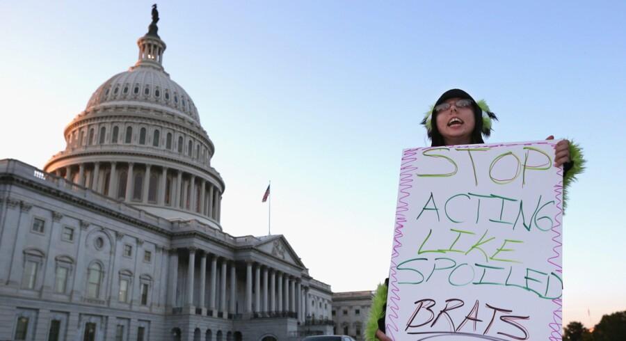 Hold op med at opføre jer som forkælede møgunger, lyder opfordringen fra denne demonstrant til de amerikanske politikere, der stadig er vildt uenige om landets budget. Foto: Getty/AFP