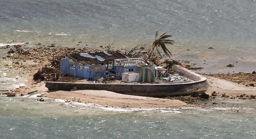 Resterne af et enkelt hus med en enkelt tilbagestående kokospalme på øenManicani nær Samar i det område, hvor tyfonen rasede.