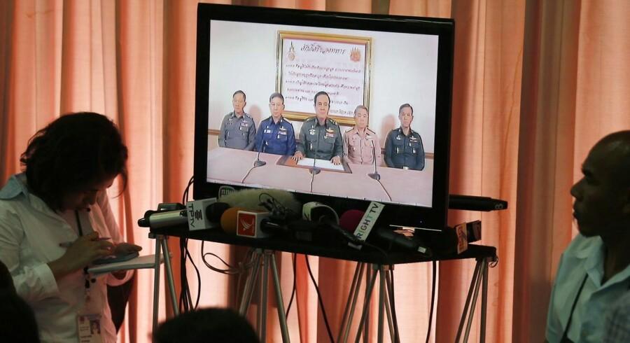 Journalister lytter til en udsendelse med militærchef general Chan-ocha efter kuppet.