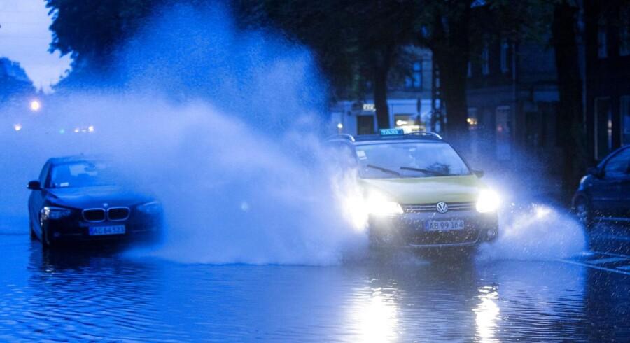 Kraftigt regnvejr ramte Østdanmark natten til søndaqg den 31. august 2014. Taxi pløjer gennem vandet på Øster Farimagsgade i København.
