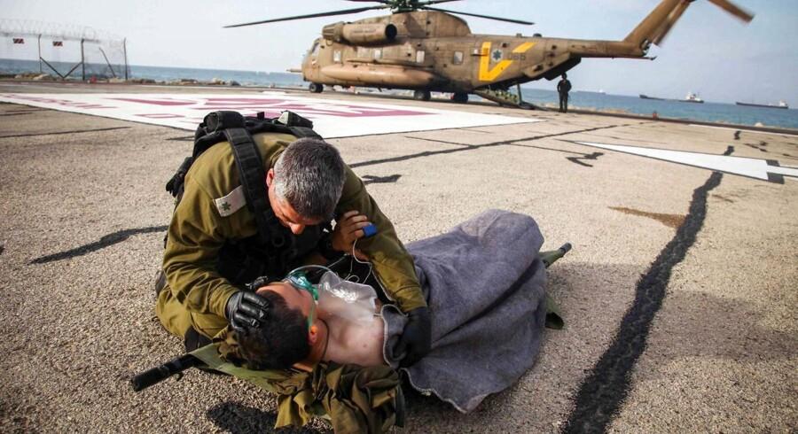 En officer tager sig af en israelsk officer ved en landingsbane på Haifas Rambam-hospital i det nordlige Israel. Tirsdag blev fire israelske soldater ramt af en avanceret vejsidebombe op ad det israelske sikkerhedshegn ved våbenstilstandslinjen. Én af soldaterne blev alvorligt kvæstet.