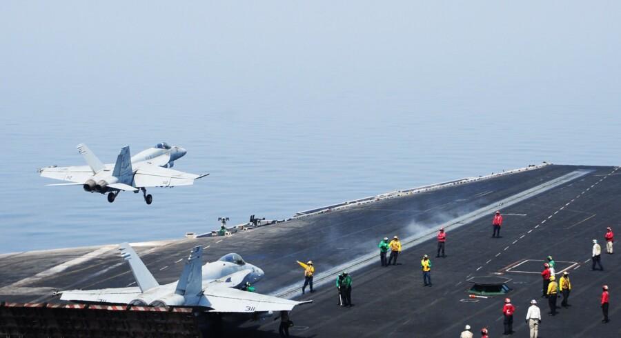Besætningsmedlemmer på dækket af det amerikanske hangarskib USS »George H.W. Bush«, som p.t. befinder sig i Den Persiske Golf, dirigerer rundt med F/A-18E Super Hornet-kampfly, der er indsat i angrebnene mod IS.?Foto: Joshua Card/AFP