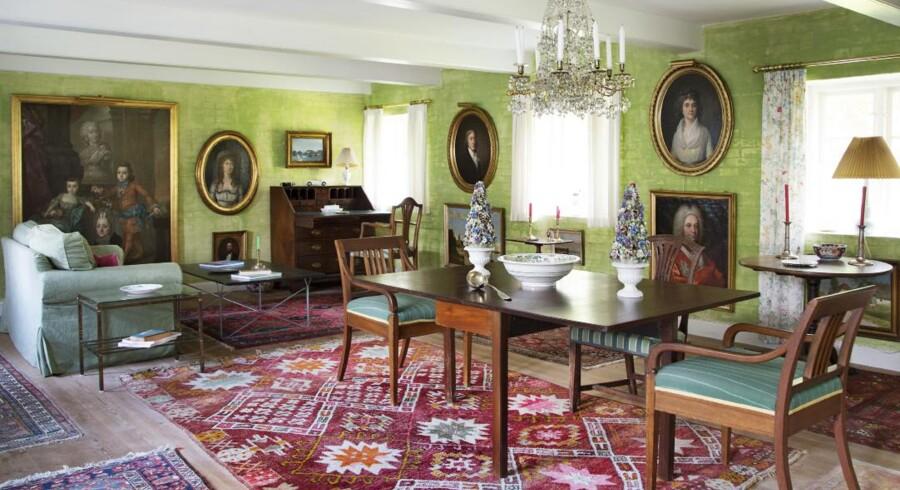 I den største af stuerne er væggene kalket i en frisk grøn farve, der danner en ensartet baggrund for det klassiske møblement.