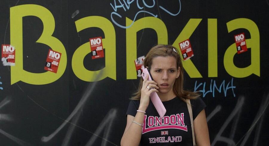En ung kvinde foran en af Bankias filialer i Madrid. Banken har været udsat for massive protester, efter det blev kendt, at den var i massive problemer.
