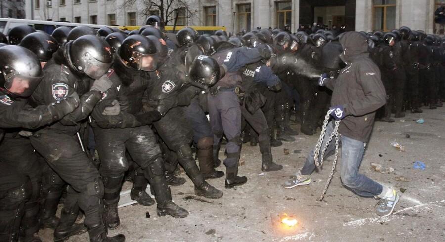 En ukrainsk tilhænger af EU-aftale sprøjter tåregas mod politiet i Kiev.