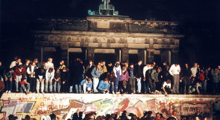 Jublende berlinere på Berlinmuren, 9. november 1989, efter at den østtyske regering har åbnet grænsen mellem Øst- og Vesttyskland. I baggrunden ses Brandenburger Tor.