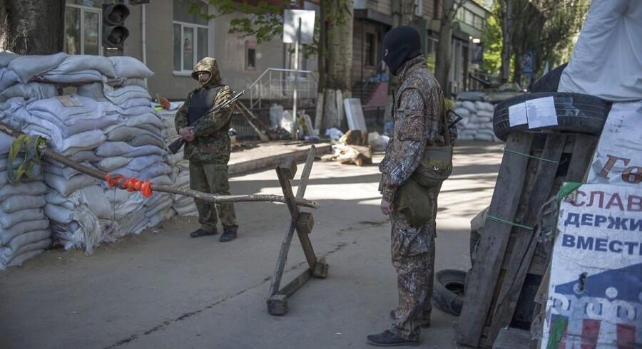 Bevæbnede prorussiske separatister ved et selvlavet checkpoint tæt på en besat offentlig bygning i Slavjansk, Ukraine, 26 April 2014.