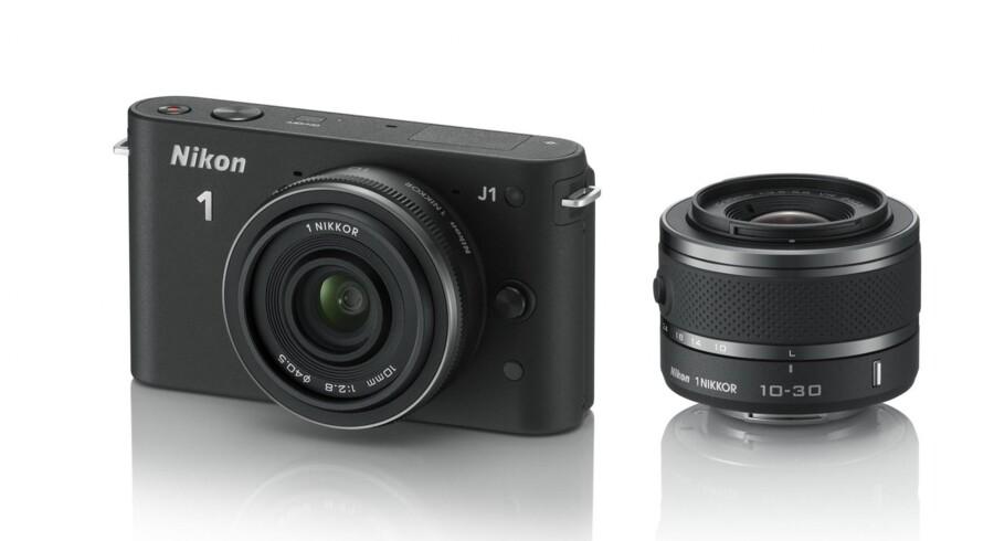 """Nikon 1-seriens mindste model J1, med en påsat 10 mm """"pandekagelinse"""" og ved siden af en 10-30 mm zoomlinse."""
