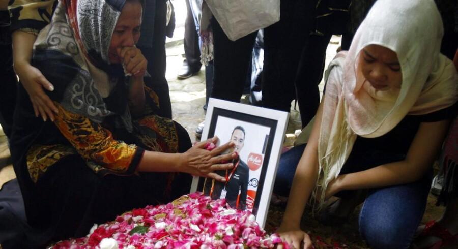Pårørende til Oscar Desano, en kabinemedarbejder, der døde i flystyrtet, sørger ved begravelsen i Klaten.