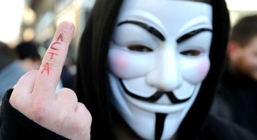 Demonstrant med Guy Fawkes-maske giver sin klare mening om ACTA-aftalen til kende.