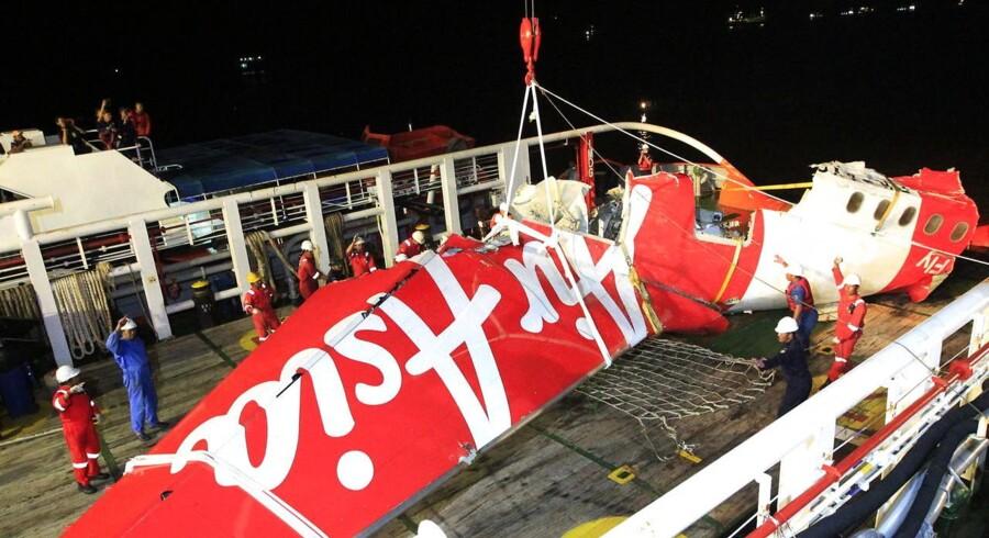 Vragdele fra det nedstyrtede AirAsia-fly løftes op af indonesiske redningsarbejdere.